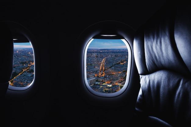 Viajando de avião, olhando pela janela do avião e vista da cidade à noite
