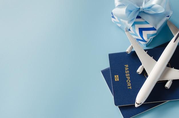 Viajando de presente. avião de brinquedo com passaportes e caixa de presente.