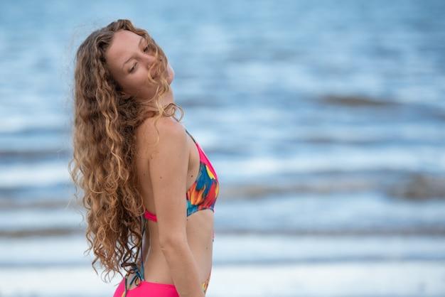 Viajando mulher na praia com cabelo loiro.