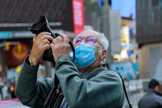 Viajando na cidade americana o novo turismo normal com máscara homem de meia idade tira foto de nova york eua