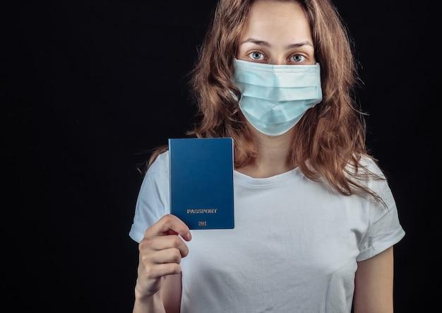 Viajando para a pandemia covid-19. mulher com uma máscara médica detém um passaporte em uma parede preta.