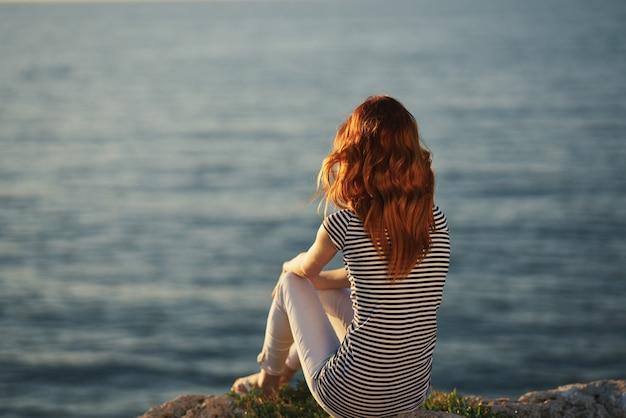 Viajante à beira-mar ao pôr do sol vista traseira