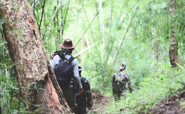 Viajante a caminhar na floresta de bambu homens caminhantes grupo de montanha de amigos andando com mochilas