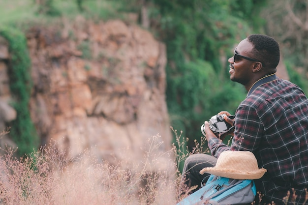 Viajante africano com mochila tirando uma foto no topo de uma montanha