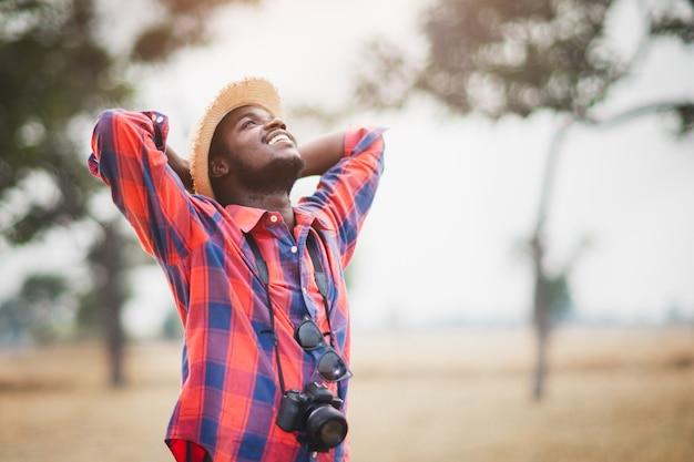 Viajante africano ou fotógrafos em pé e viajando nos campos de savana