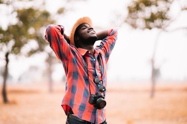 Viajante africano sorrindo e aproveitando seu tempo de lazer na natureza