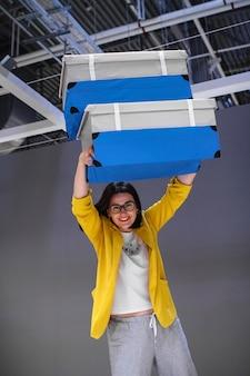 Viajante alegre da menina com as duas malas de viagem azuis em um fundo cinzento.