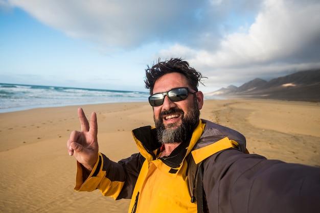 Viajante alegre, feliz, homem tirando uma foto de selfie em um lugar selvagem e pitoresco, praia solitária com montanhas em backgorund, estilo de vida alternativo e atividades de lazer ao ar livre com férias de aventura