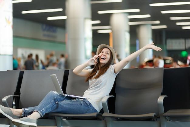 Viajante alegre, turista, mulher, trabalhando no laptop, falando no celular, ligar para um amigo, reservar um táxi em um hotel, espalhar as mãos, esperar no saguão do aeroporto