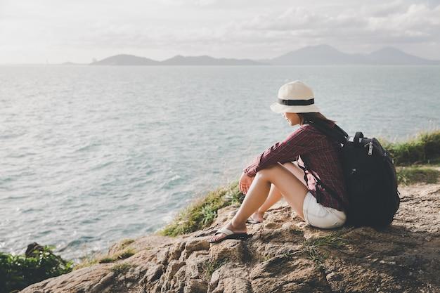 Viajante asia mulher sentada no penhasco do mar