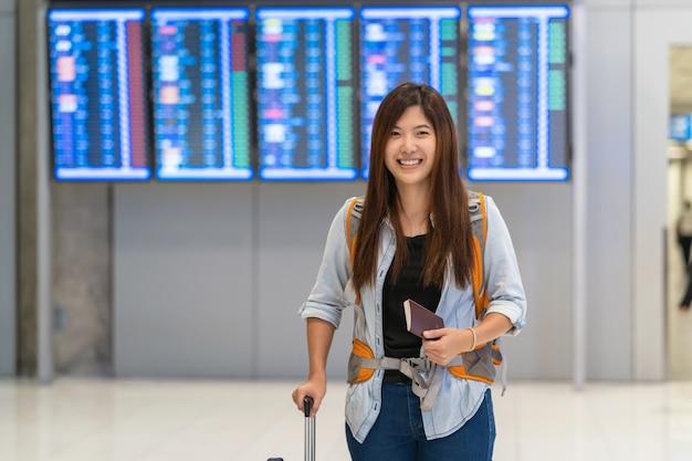 Viajante asiático com bagagem com passaporte andando sobre a placa de voo para check-in