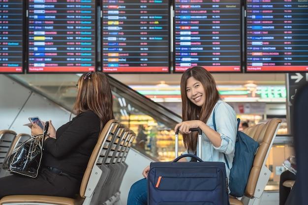 Viajante asiático com bagagem com passaporte sentado sobre a placa de voo para check-in