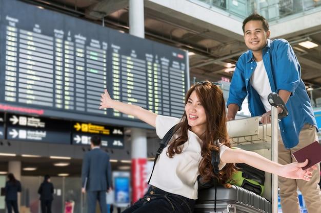 Viajante asiático dos pares com as malas de viagem no aeroporto.
