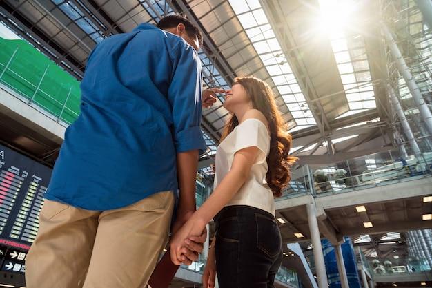Viajante asiático dos pares com guardar o passaporte no aeroporto.