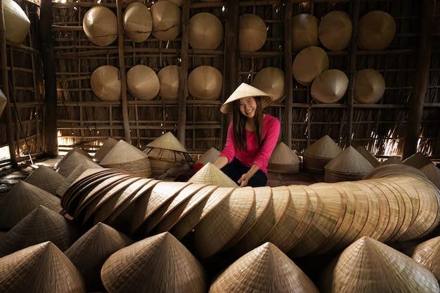 Viajante asiático feminino artesão fazendo o tradicional chapéu de vietnam na antiga casa tradicional
