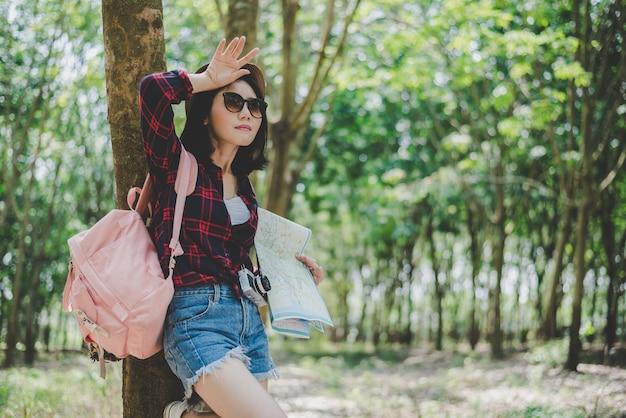 Viajante asiático feminino cansativo de perdeu seu caminho na floresta