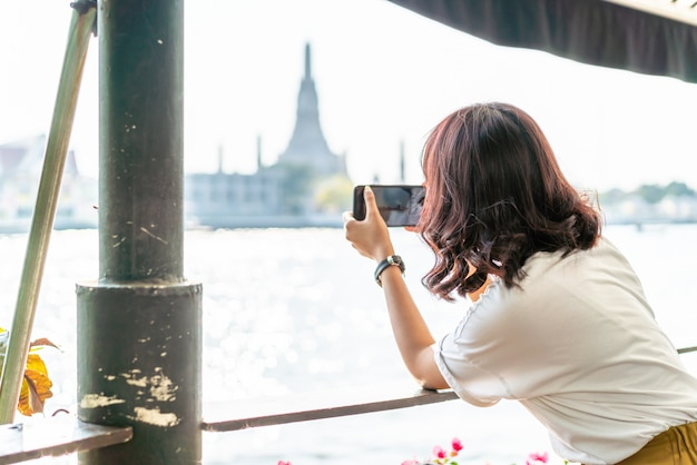 Viajante asiático mulher tirando uma foto no café