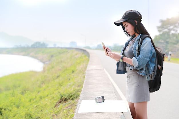 Viajante asiático novo com a trouxa que procura a direção no mapa de lugar e que usa o telefone esperto ao viajar durante férias do feriado