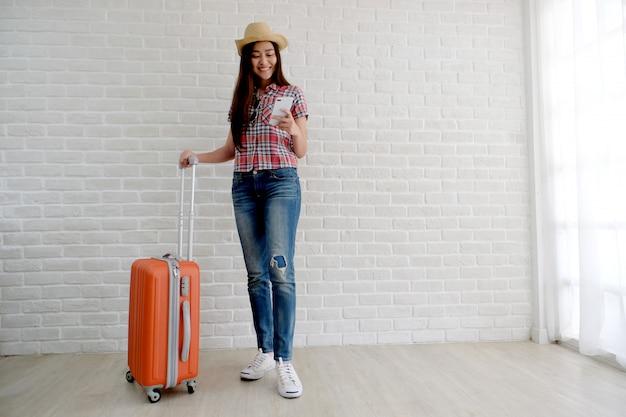 Viajante asiático novo da mulher que guarda o telefone e a bagagem espertos no quarto branco