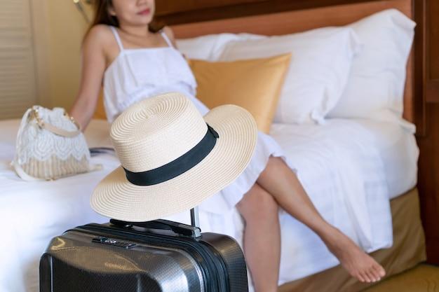Viajante asiático novo no vestido branco que relaxa olhando através de uma janela no quarto de hotel após a chegada com bagagem no primeiro plano.