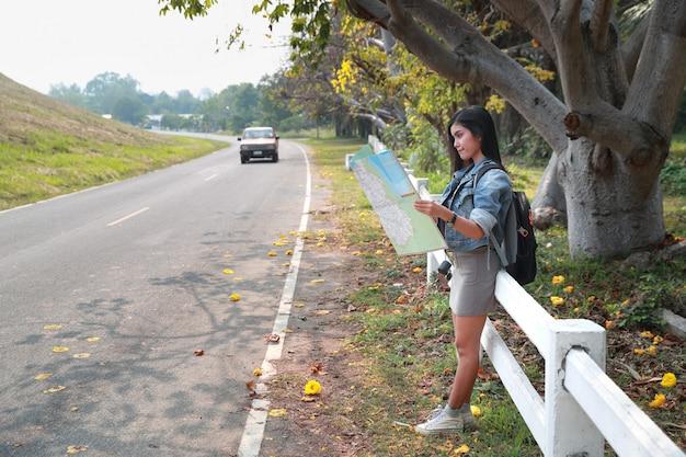 Viajante asiático novo que procura a direção no mapa de lugar ao viajar durante férias do feriado