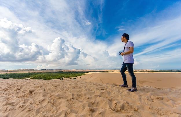 Viajante asiático novo que toma a foto com a câmera mirrorless nas dunas de areia brancas mui ne
