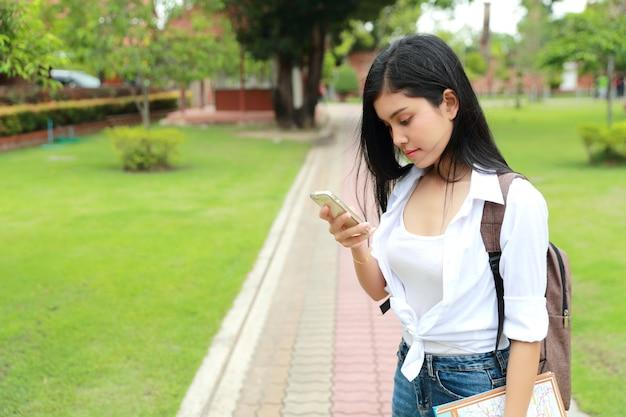 Viajante asiático novo que usa o telefone celular e guardando o mapa no templo ao viajar durante férias do feriado