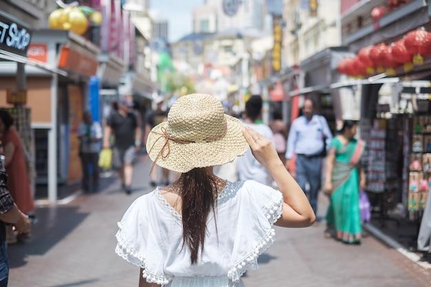 Viajante asiático que anda no mercado de rua de chinatown em singapura.