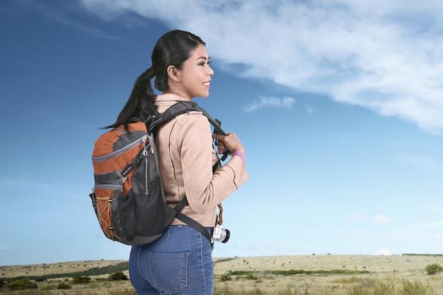 Viajante asiático sorridente carregando mochila em viagem