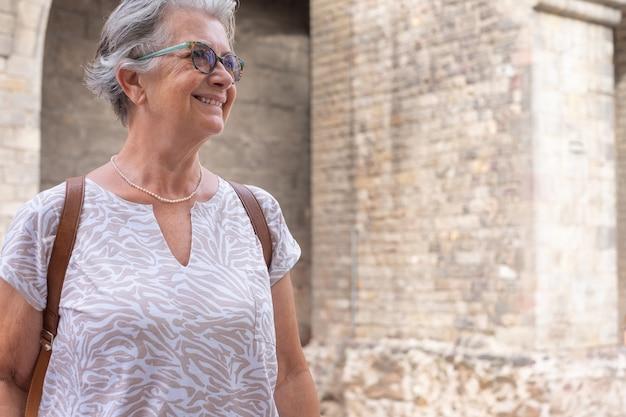 Viajante atraente idosa visitando a catedral de barcelona feliz aposentada aproveitando as férias