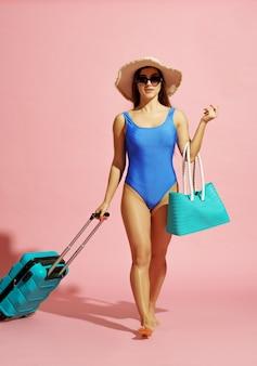 Viajante bonita em poses de maiô e chapéu com mala rosa