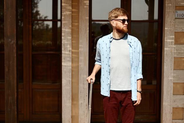 Viajante bonito com a barba por fazer do lado de fora do hotel com uma mala esperando a namorada para o check-in