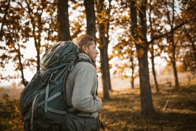 Viajante, caminhando ao longo de um caminho de floresta entre as árvores