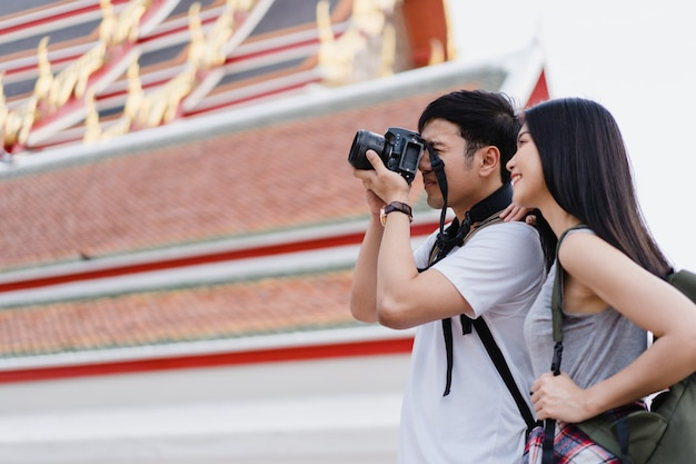 Viajante casal asiático usando a câmera para tirar uma foto ao passar a viagem de férias em bangkok, tailândia