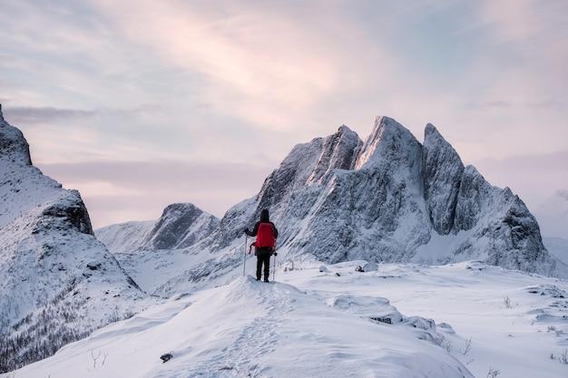 Viajante com bastões de caminhada no topo da montanha segla no inverno na ilha senja