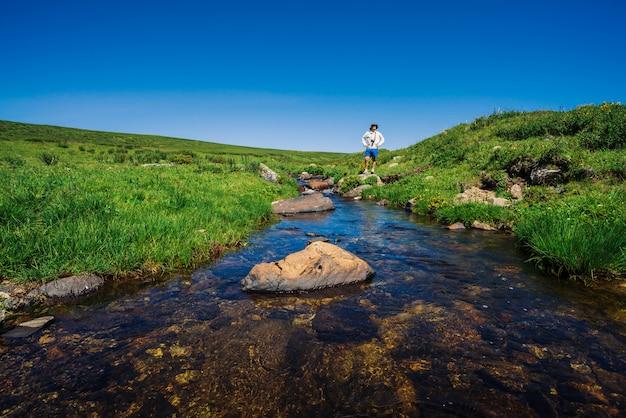 Viajante com câmera na pedra no riacho de montanha.