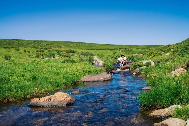 Viajante com câmera na pedra no riacho de montanha