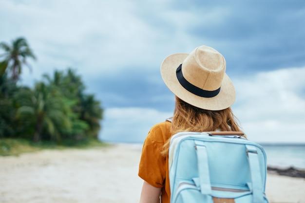 Viajante com chapéu de mochila na cabeça e vestido de verão laranja vista traseira