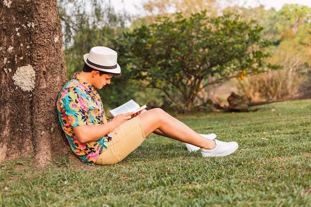 Viajante com chapéu e camisa florida, lê um livro no parque. turista deitado em uma árvore lê um livro. homem tropical lê um livro.
