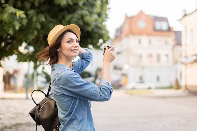 Viajante com chapéu tirando fotos ao ar livre