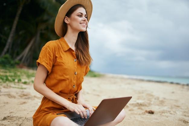 Viajante com laptop freelancer praia verão areia chapéu vestido de verão