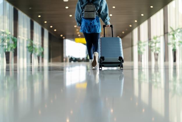 Viajante com mala andando com transporte de bagagem no terminal do aeroporto