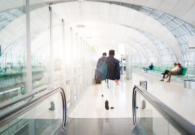 Viajante com mala de viagem ou bagagem andando na passarela do terminal do aeroporto