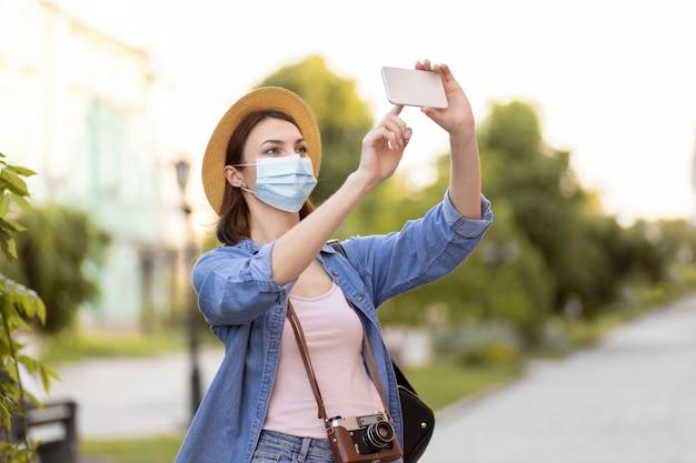 Viajante com máscara facial e chapéu tirando fotos