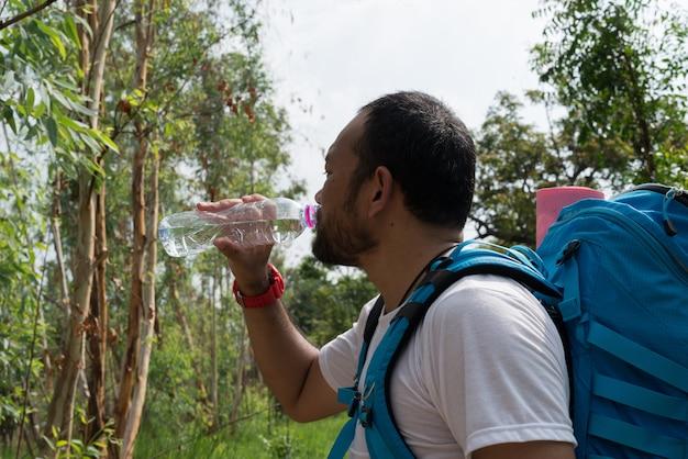 Viajante com mochila andando no cenário da floresta ao ar livre. viagem, aventura