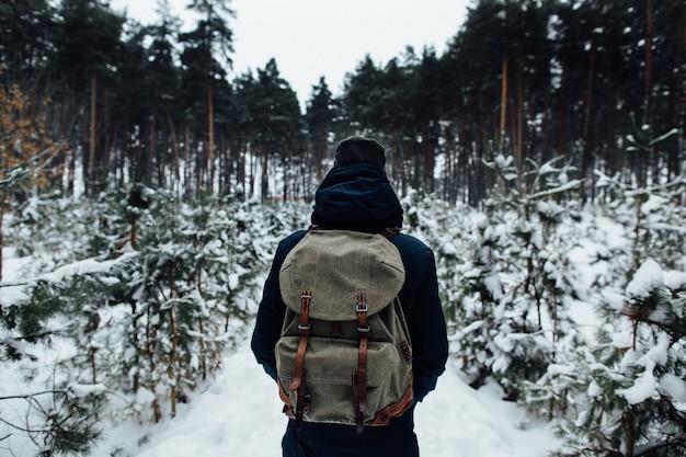 Viajante com mochila de viagem, apreciando a paisagem de neve na floresta de pinheiros de inverno
