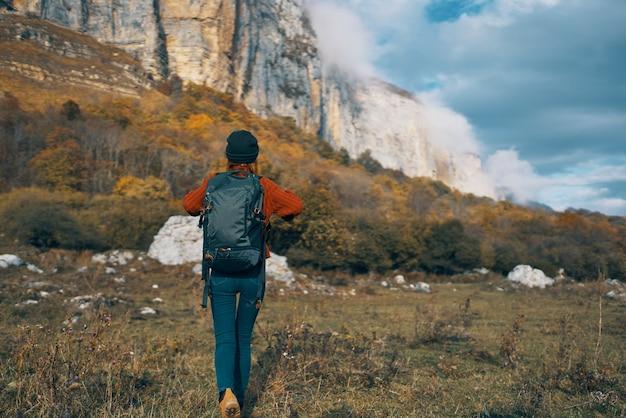 Viajante com mochila descansando nas montanhas ao ar livre em paisagem de outono, céu azul e rochas