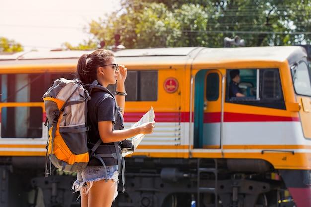 Viajante com mochila e chapéu, olhando o mapa