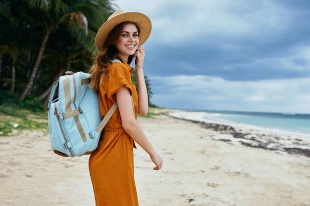 Viajante com mochila na natureza se volta para a câmera e sorri