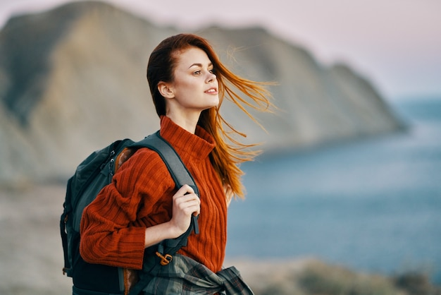 Viajante com um suéter vermelho perto do mar na natureza com uma mochila nas costas e montanhas no